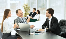 Business partners are discussing a plan of cooperation against the background of team work Stock Photography