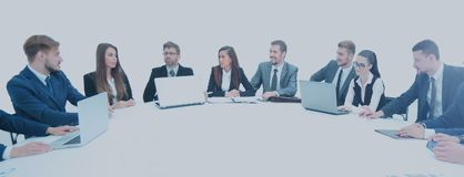 Business partners with documents and laptops sitting around the Stock Photography