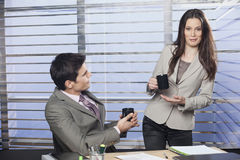 Business partners drinking coffee in office. Friendly business partners drinking coffee in office stock photography