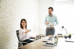 Business partners drinking coffee in an office Royalty Free Stock Photos