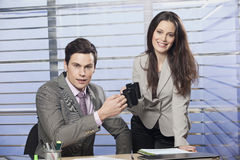 Business partners drinking coffee in office. Friendly business partners drinking coffee in office Stock Images