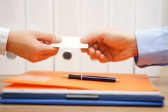 Business partners are exchanging business cards over documents a Royalty Free Stock Photos