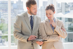 Business partners going over document on clipboard Stock Image