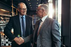 Business partners handshake at cafe. Two senior businessmen meeting at cafe shaking hands. Business partners handshake at modern coffee shop royalty free stock image
