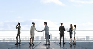 Business partners handshake . Mixed media Royalty Free Stock Images