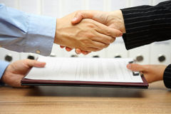 Business partners are handshaking and exchanging contract after Stock Photos