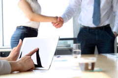 Business partners handshaking over business objects on workplace. businesswoman working with digital tablet royalty free stock photos