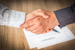 Business partners handshaking over successful conclusion Stock Images