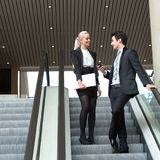 Business couple talking on escalator. Royalty Free Stock Photo