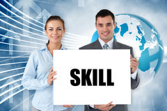 Business partners holding card saying skill Stock Image