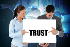 Business partners holding card saying trust Stock Photography