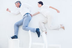 Business partners jumping over chairs Stock Photos