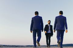 Business partners. Leaders have business meeting. Businessmen with confident faces. In formal suits on blue sky background, copy space. Company CEOs walk Royalty Free Stock Image