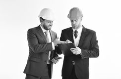 Business partners look at building plan. Engineers with beards and happy faces. Architects discuss project. Entrepreneur and architect look confident stock photos