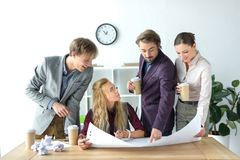 Business partners looking at flipchart paper Stock Images