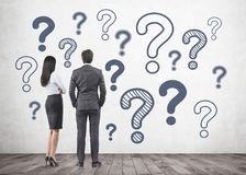 Business partners looking at wall, question marks Stock Photos