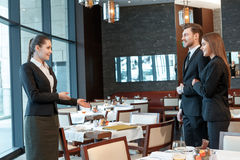 Business partners meet at lunch. Feeling at ease at the meeting. Female business manager suggests place for lunch to her business partners in the restaurant royalty free stock photo