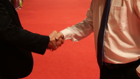 Business partners meet and shake hands on red stock video footage