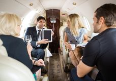 Business Partners Meeting In Private Jet. Businessman showing project on digital tablet to partners in private jet stock photos