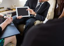 Business Partners Meeting In Private Jet. Cropped image of businessman showing digital tablet to partners in private jet Royalty Free Stock Photo