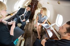 Business Partners Meeting In Private Plane. Businessman showing project on digital tablet to partners in private plane Royalty Free Stock Image