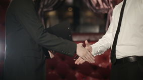 Business partners men doing a handshake. Slow motion. Close up stock video footage