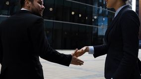 Business partners men and women doing a handshake. Back view. People are attractive hansome and very confident. Modern glass building at background. Slow stock video footage