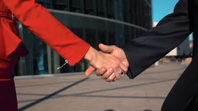 Business partners men and women doing a handshake. Two Business partners men in black suit and women in red bright dress do a hand-shake with glass business stock footage