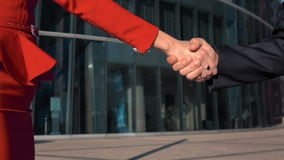 Business partners men and women doing a handshake. Two Business partners men in black suit and women in red bright dress doing a handshake with glass business stock video footage