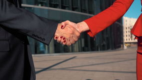 Business partners men and women doing a handshake. Two Business partners men in black suit and women in red bright dress and manicure doing a handshake with stock video