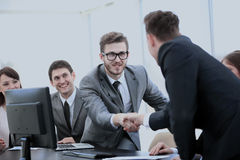 Business partners near your Desk to shake hands as a sign of coo Royalty Free Stock Photos