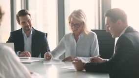 Business partners negotiate sign contract handshake at group meeting. Old businesswoman and middle aged businessman partners negotiate sign contract handshake at stock video