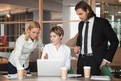 Business partners negotiating about strategies using laptop. Businesswoman sharing business ideas pointing at laptop, presenting project, explaining online Stock Image