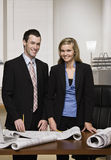 Business partners posing with blueprints. Portrait of Business partners posing with blueprints Royalty Free Stock Photo