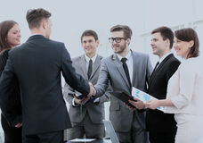 Business partners in the presence of a business team shake hands Royalty Free Stock Images