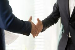 Business partners reaching consensus on meeting. Close up photo of businessmen hands stretched out for handshaking. Business partners welcoming each other before Stock Photography
