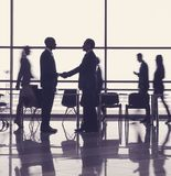 Business partners reaching working consensus. Two men standing in business center and shaking hands. Colleagues walking on background royalty free stock photos