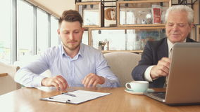 Business partners shake hands at the cafe. Two caucasian business partners shaking hands at the cafe. Young bearded guy sitting down near his older companion