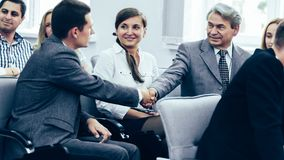 Business partners shake hands in the conference room. In a good mood stock image