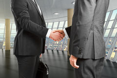 Business partners shake hands in empty room Stock Photo