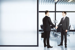 Business partners shake hands in modern conference room with bla Stock Image