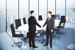Business partners shake hands in modern conference room Royalty Free Stock Images