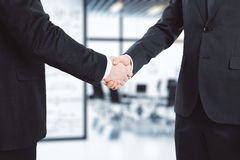 Business partners shake hands in modern conference room Royalty Free Stock Photography