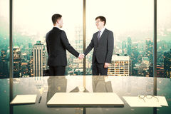 Business partners shake hands in modern office with night megapo Royalty Free Stock Photo