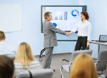 Business partners shake hands after a  presentation Stock Images