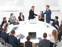 Business partners shake hands at the talks near the round table Royalty Free Stock Photos