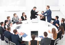 Business partners shake hands at the talks near the round table Royalty Free Stock Images