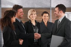 Business partners shaking hands. Happy business partners shaking hands in meeting room, smiling Royalty Free Stock Photo