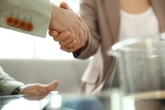 Business partners shaking hands after meeting. Closeup royalty free stock photo
