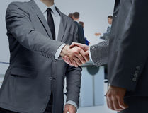 Business partners shaking hands in meeting hall Stock Photos